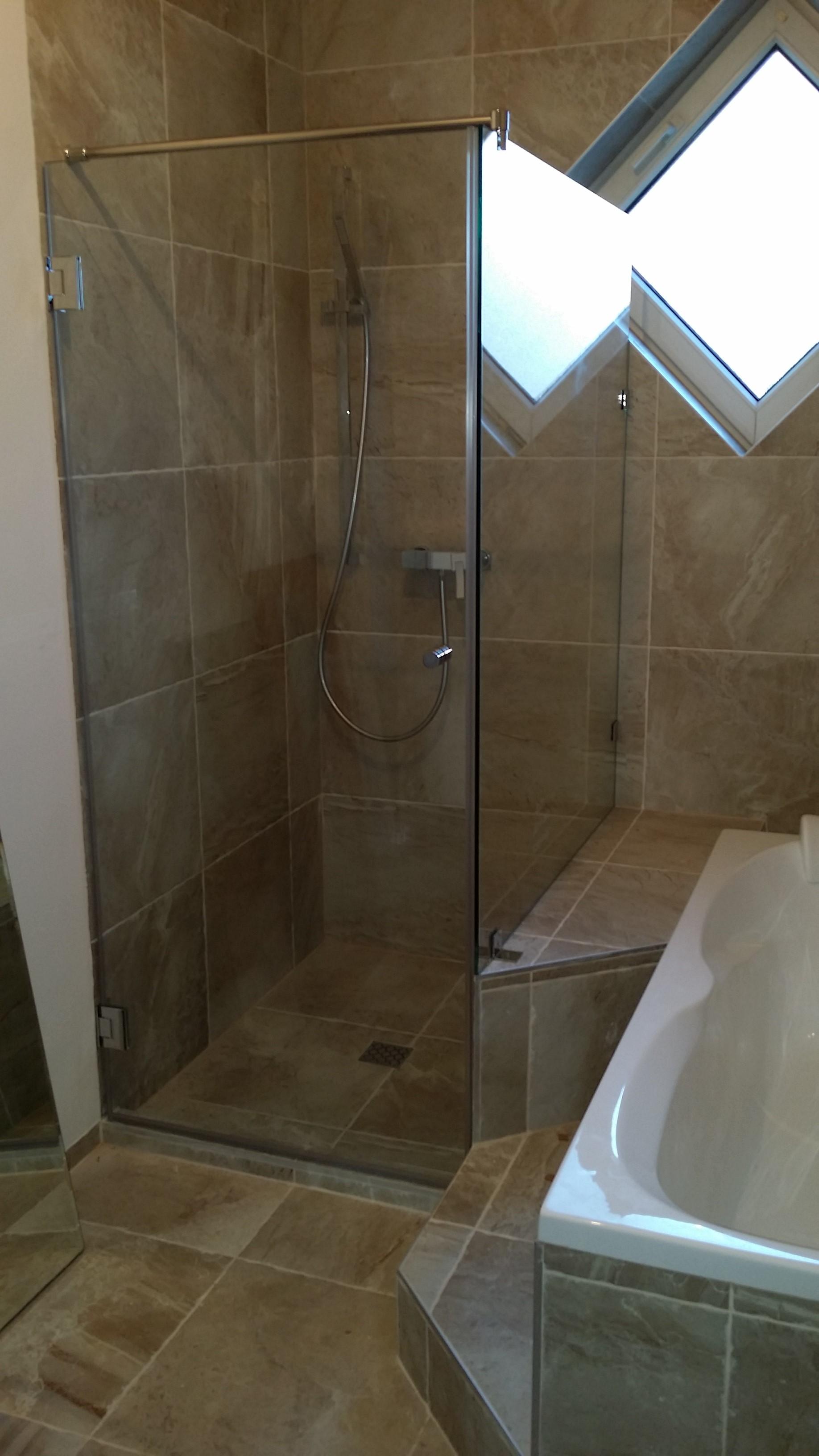Egyenes zuhanyfal egy falról nyíló ajtóval és egy fix résszel